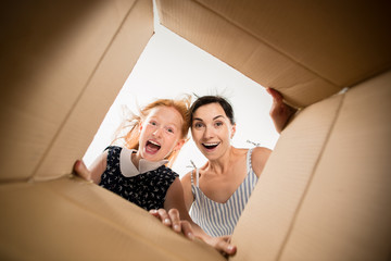 The surprised mom and daughter unpacking, opening carton box and looking inside. The package, delivery, surprise, gift lifestyle concept. Human emotions and facial expressions concepts