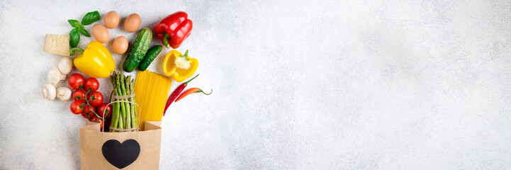 Healthy food background. Healthy food in paper bag vegetables, pasta, eggs, cheese and mushrooms on white. Ingredients for cooking pasta. Shopping food supermarket concept. Long format with copy space Fototapete