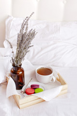 Morning breakfast in bed wooden tray with a cup of tea, sweet colorful french macaroons, love letter, bouquet of lavender. Top view Morning at Hotel or at home. Background Concept Cozy morning