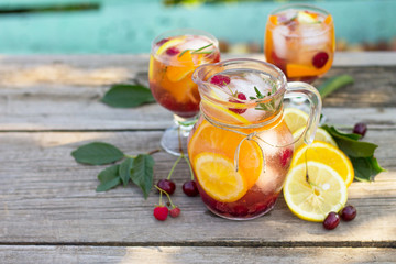 Homemade refreshing wine sangria or punch with fruits in glasses. Sangria cocktails with fresh fruits, berries and rosemary. On a wooden rustic table, with a jug and ingredients. Copy space.