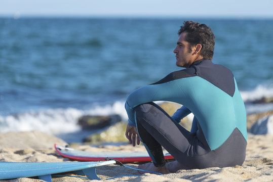 Back view of man in wetsuit sitting with surfing board on beach looking at ocean.
