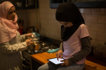 Muslim mother cooking while daughter using digital tablet