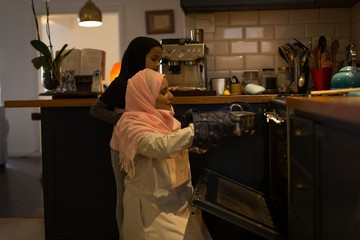 Muslim woman and daughter using the oven in the kitchen