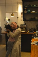 Muslim mother and daughter embracing each other in the kitchen