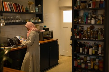 Muslim woman looking at the printout in kitchen