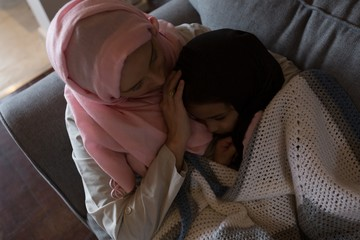 Muslim woman putting her daughter to sleep