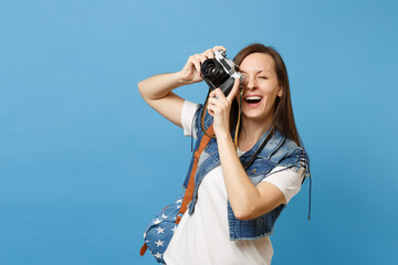 Portrait of young joyful woman student with opened mouth with backpack take pictures on retro vintage photo camera isolated on blue background. Education in university. Copy space for advertisement.