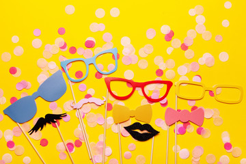 Photo booth props glasses, mustache, lips on a pink background flat lay. Birthday parties and weddings.