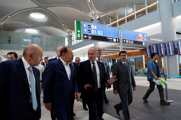 Turkey's Transport and Infrastructure Minister Turhan chats with Kalyoncu, Chairman of Kalyon Construction, as they walk at the international terminal of the city's new airport under construction in Istanbul