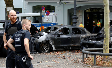 German police officers are seen beside burned cars at Kurfurstendamm boulevard in Berlin