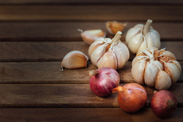 Garlic and onion on wooden background have cloves top