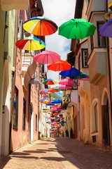 Colored umbrellas decorates alley in old town in Chiusa Italy