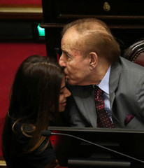 Senator and former Argentine President Carlos Menem shares a moment with his daughter Zulema Menem as lawmakers meet to debate and vote on a bill that would legalize abortion, in Buenos Aires