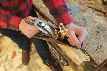 Male carpenter using plane tool in workshop