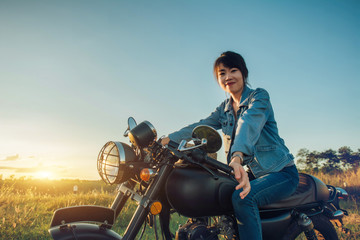 Young woman drive with motorcycle on street, enjoying freedom and active lifestyle, having fun on a bikers tour on sunset background.