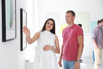 Young couple at exhibition in art gallery