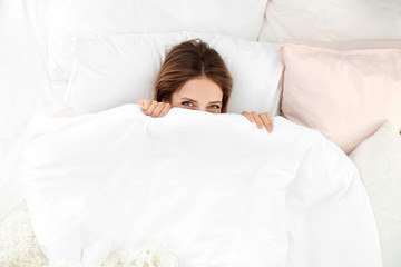 Young woman lying on soft pillows and hiding under blanket in bed at home