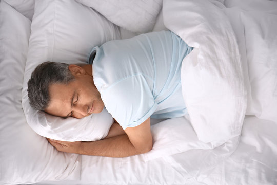 Man sleeping on comfortable pillow in bed at home, top view