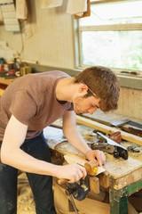 Male carpenter using marking gauge in workshop