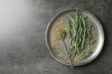 Plate with dried rosemary and twigs on table, top view