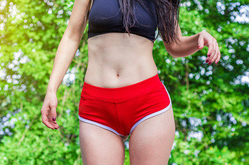 Hips of a girl, slender legs in red shorts panties
