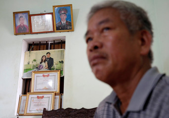 Vietnam War veteran Diem Trong Thach who was exposed to Agent Orange sits front of him and his wife's portraits at his house in Bac Ninh province