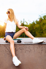Portrait of a beautiful girl in the Park with a skate, summer mood
