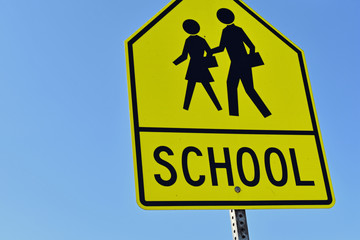 Yellow SCHOOL Signage against Blue Sky