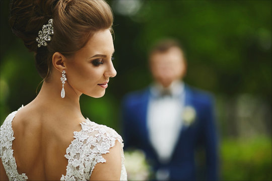 Beautiful and fashionable brunette model girl with bright make-up and with wedding hairstyle, young stylish bride in trendy lace dress with naked back looks back and posing at open air
