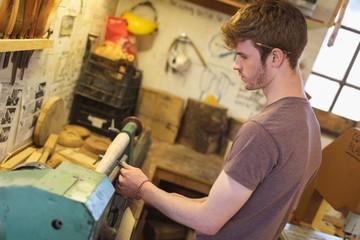 Male carpenter sharping tool on machine