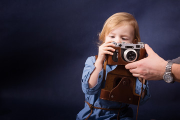 Cheerful little girl learning to do photos with the retro camera and dad helps her