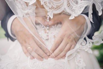 wedding photo of wedding rings on the groom's hands. heart