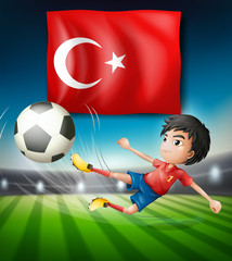 Boy kicking a soccer ball infront of turkish flag