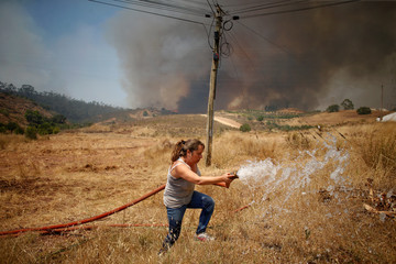 A women pours water on her terrain while the fire approaches Pinheiro e Garrado, near Silves