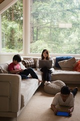 Mother using laptop while kids using digital tablet in living