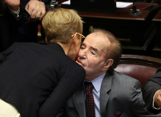 Senator Silvina Garcia Larraburu greets Senator and former Argentine President Carlos Menem as lawmakers meet to debate and vote on a bill that would legalize abortion, in Buenos Aires