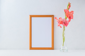 Mockup golden frame and pink flowers in a vase on a light background