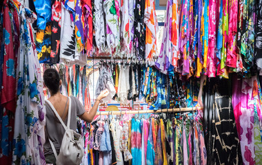 A woman looking at different colorful shirts while clothes shopping