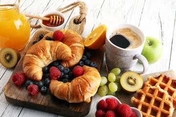 Delicious breakfast with fresh croissants and ripe berries on table