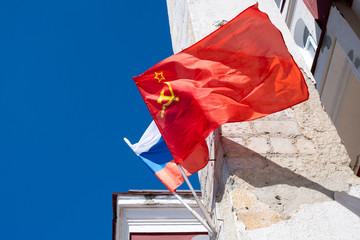 flag of the USSR and flag of Russia on the wall of the old building under the blue sky