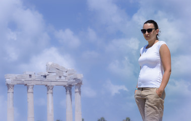 brunette girl in a white t-shirt and sunglasses stands. In the background, the ruins of an ancient temple in a blue haze. mock up for prints