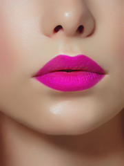 Close-up of woman's lips with bright fashion pink glossy makeup. Macro magenta lipgloss make-up. Sexy pink lip makeup. Highly saturated color. Lipstick
