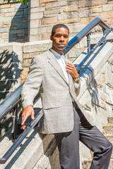 Portrait of Young African American Businessman in New York City, wearing patterned blazer, white undershirt, black pants, wristwatch, standing on rock stairs by railing, fist putting on chest, looking