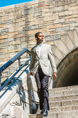 Young Happy African American Businessman traveling in New York City, wearing patterned blazer, white undershirt, black pants, leather shoes, walking down rock stairs by railing, looking around..
