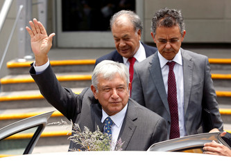 Mexican President-elect Lopez Obrador waves after being formally installed as the country's next president, outside the headquarters of the electoral authority in Mexico City