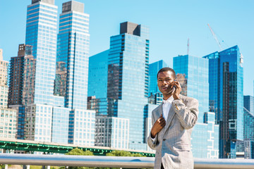 Young African American Businessman traveling in New York City, wearing patterned blazer, white shirt, standing in business district with high buildings of Manhattan under sun, talking on cell phone..