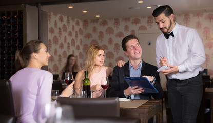 Adult waiter taking order in restaurant