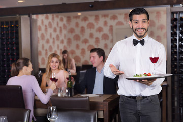 Waiter holding tray at restaurant with customers