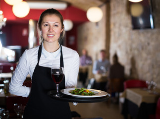 Young woman waitress with serving tray welcoming