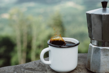 coffee the outdoors. Adventure, travel, tourism and camping concept. Hiker drinking tea from mug at camp